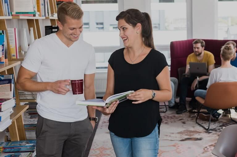 Eine Person zeigt einer anderen ein Magazin der App-Entwicklung
