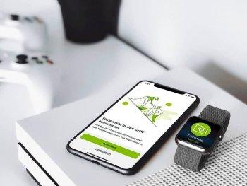 Smartphone mit digitaler Gesundheitsanwendung liegt neben Smartwatch mit der gleichen Anwendung auf einer Konsole