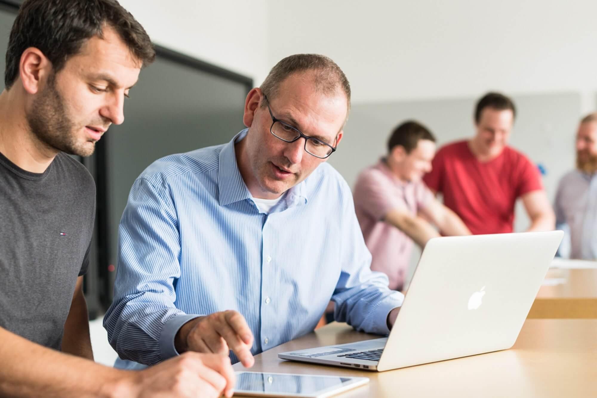 Zwei Personen führen am Laptop und iPad eine Bedarfsanalyse durch