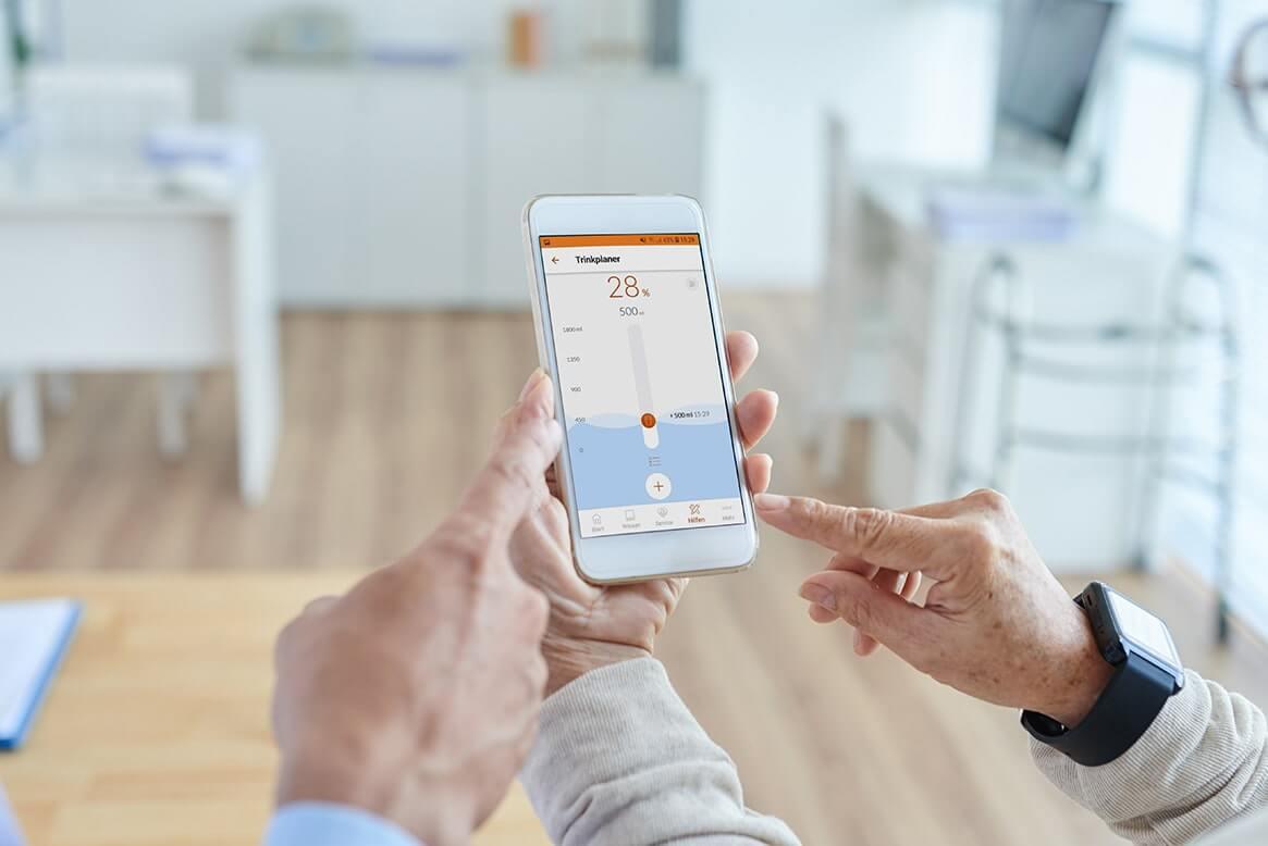 Arzt erklärt Patient Health-App auf dem Smartphone
