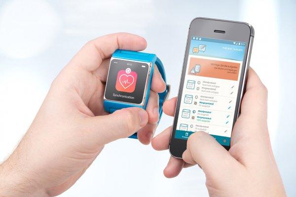 Person hält Smartwatch neben Handy mit der dazugehörigen Gesundheitsanwendung