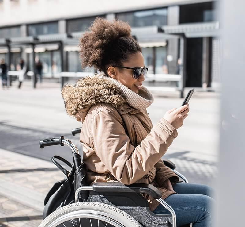 Frau sitzt im Rollstuhl und hält Smartphone in der Hand und nutzt einen mobilen Assistenten