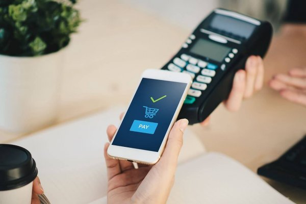 Person zahlt kontaktlos mit dem Smartphone