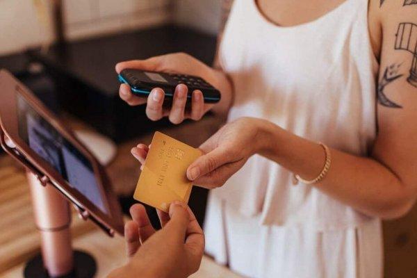 Mitarbeiterin eines Geschäftes erhält durch App Informationen am PoS