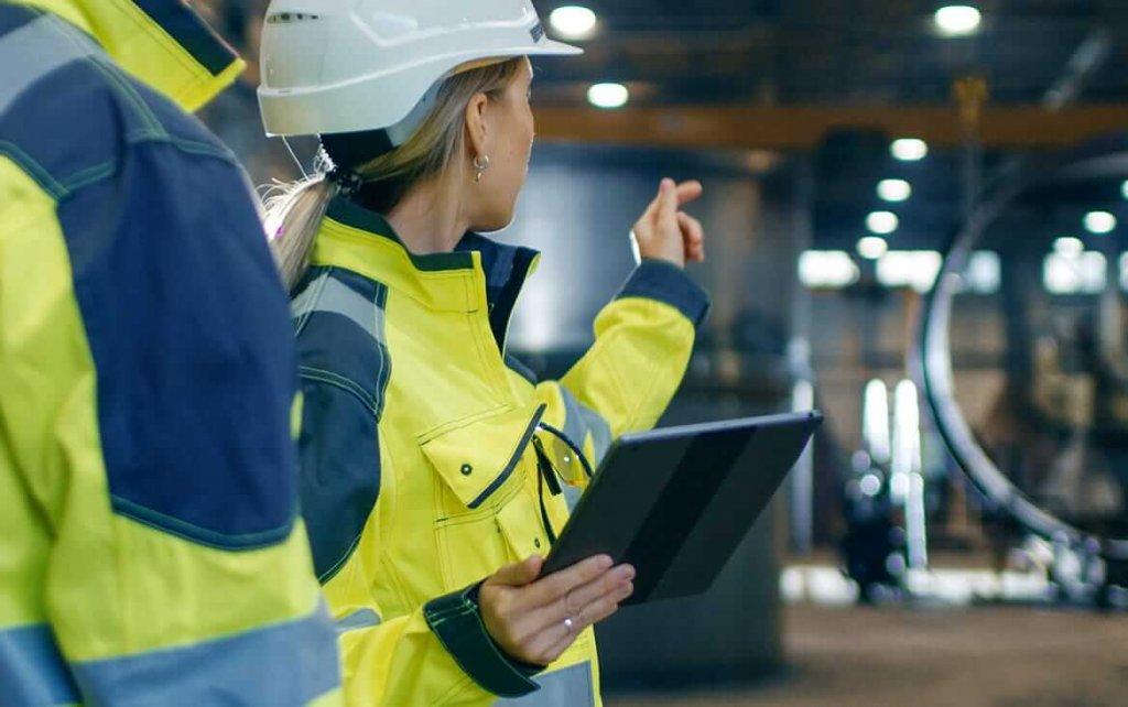 Frau zeigt Kollegen Infos auf dem iPad im Rahmen der Mobile Auftragsabwicklung