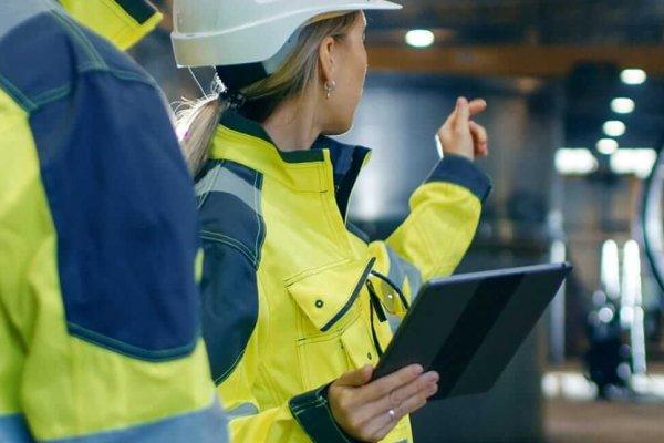 Frau zeigt Kollegen Infos auf dem iPad im Rahmen derMobile Auftragsabwicklung