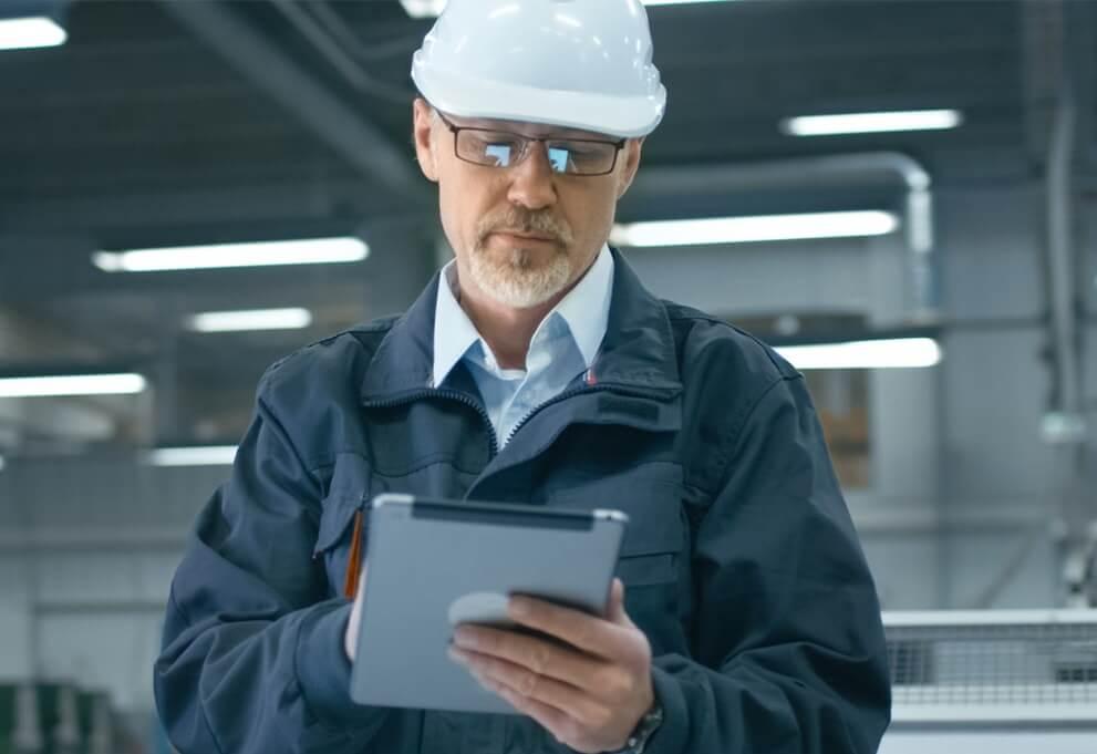 Servicetechniker mit Helm hält iPad mit Field Service App in der Hand