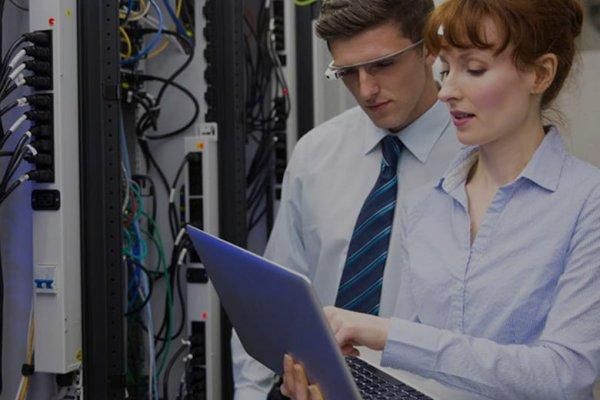 Zwei Personen stehen mit einem Laptop vor einer Maschine, eine Person trägt eine Smart Glass